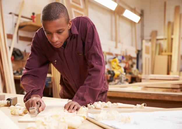 apprentice-planing-wood-in-carpentry-workshop-PE5N7AJ