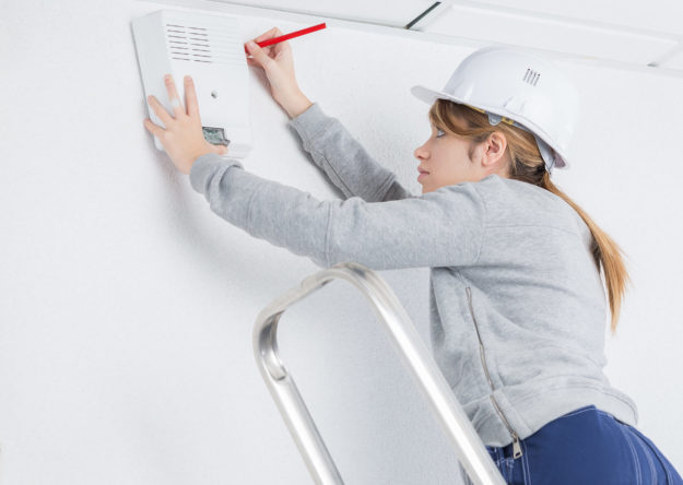female-electrician-installing-alarm