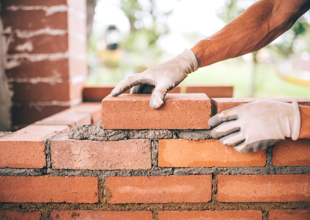 professional-construction-worker-laying-bricks-PRD8TS7