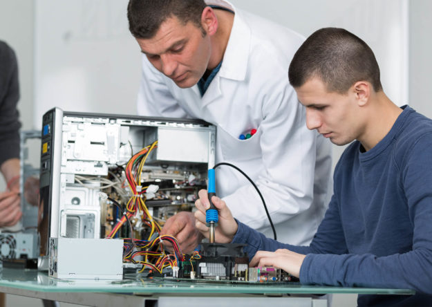 teacher-assisting-young-man-fixing-computer