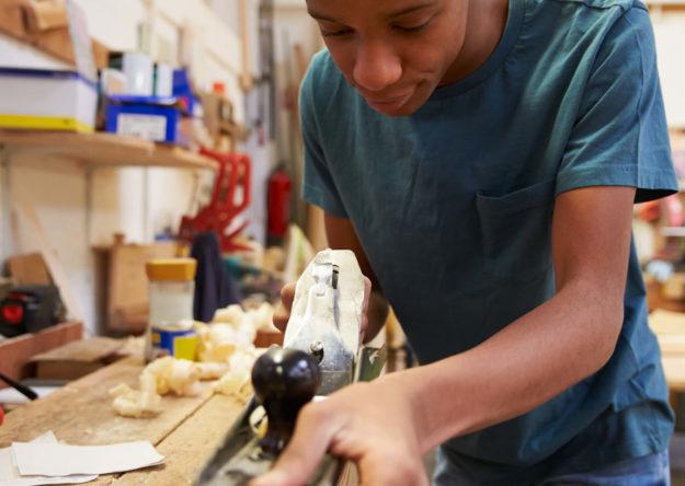 apprentice-planing-wood-in-carpentry-workshop-PSEQNDU