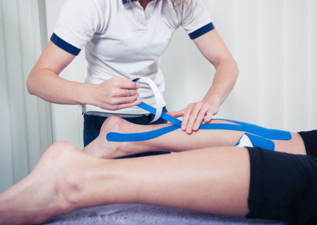 Physiotherapist is applying kinesio tape to a patient's leg