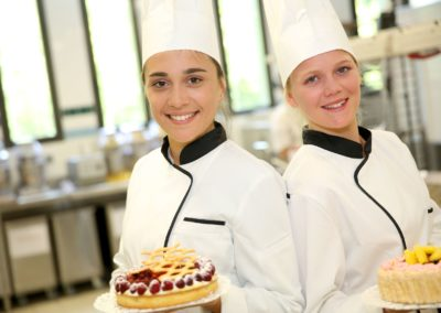 Students girls in pastry holding cakes