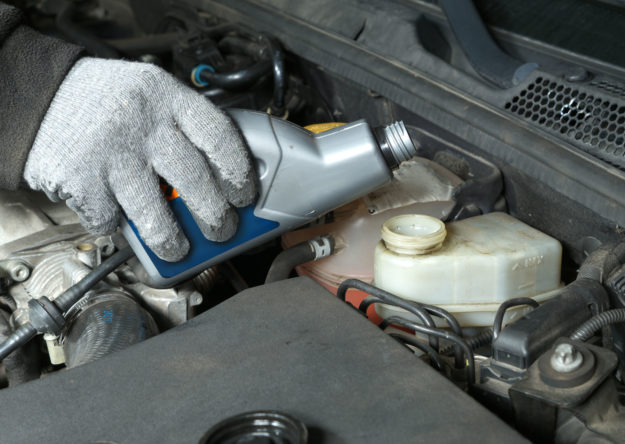 Auto mechanic topping up brake fluid in the vehicle