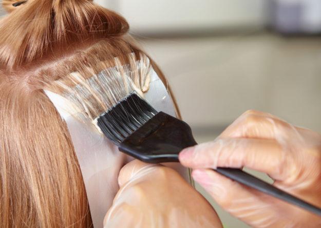 Technician coloring hair