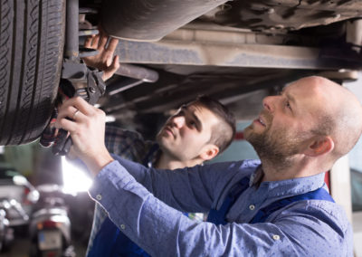 Two car mechanics checking up pressure in tires at garage