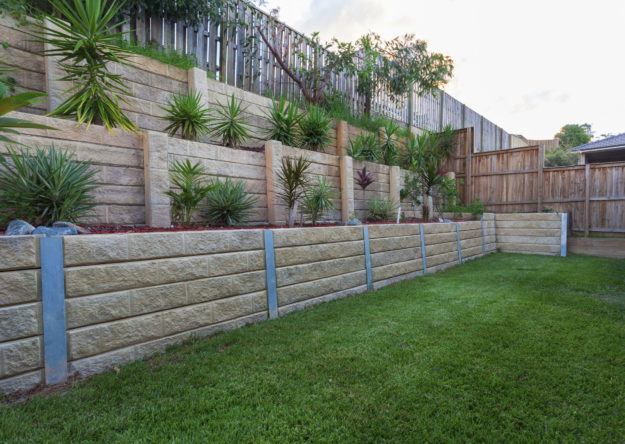 Multi-level retaining wall with plants in backyard