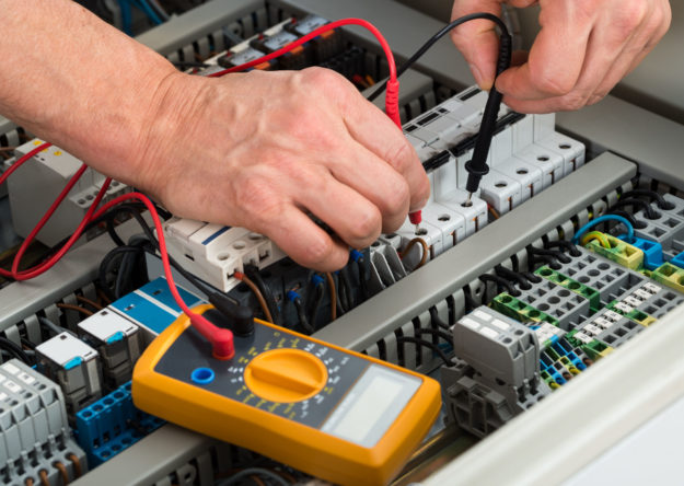 Close-up of a male electrician checking fuse with multimeter