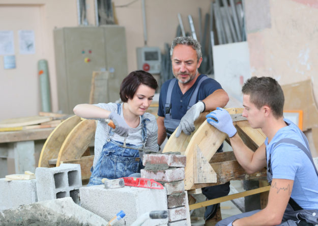 Instructor teaching students brick laying