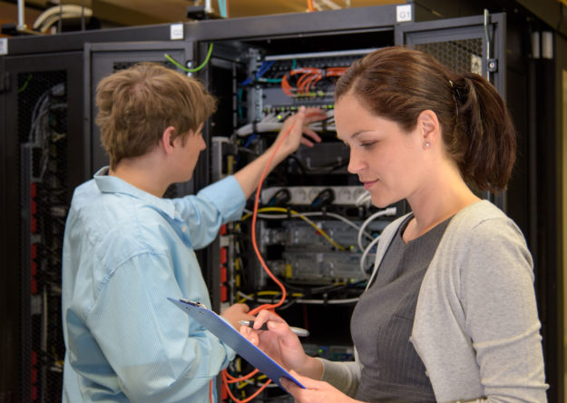 Team of it specialists in datacenter working by network servers