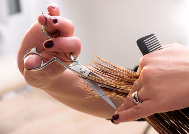 Hairdresser trimming the ends on the hair of a client with professional scissors and a comb, close up view of her hands