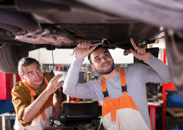 Two car mechanics at workshop at work.